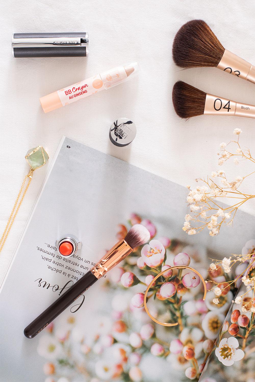 Le BB crayon Erborian posé sur un magazine ouvert sur un drap blanc au milieu d'élément de maquillage