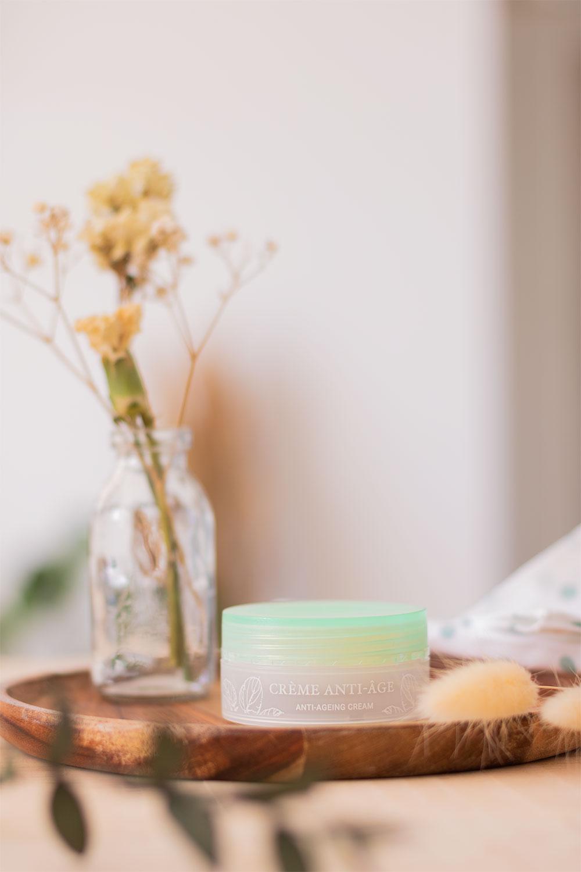 Product photography de la crème naturelle anti-âge de la marque Esthética Pure Nature, posée sur un support en bous au milieu des fleurs