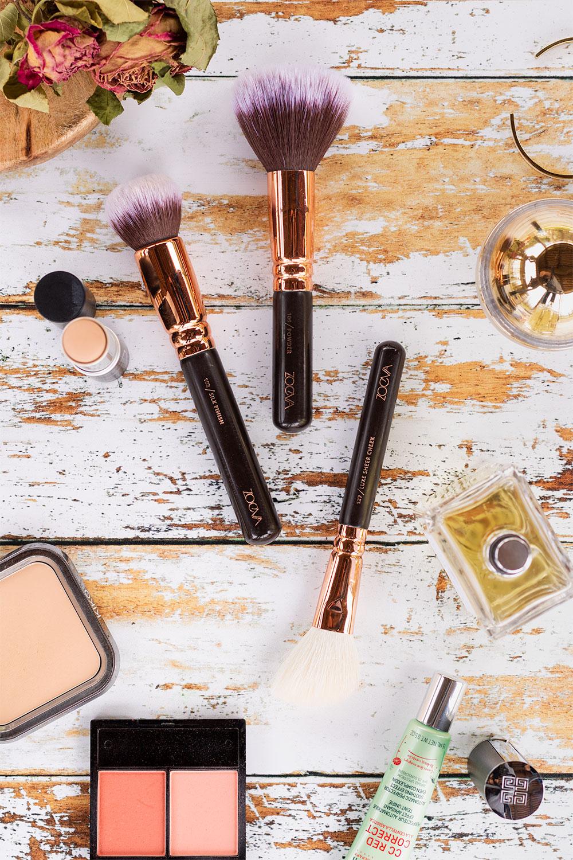 Zoom sur 3 pinceaux pour le teint de Zoeva, posé au milieu de make-up sur une table blanche en bois vintage