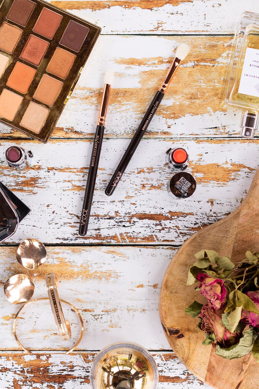 Zoom sur 2 pinceaux pour les yeux de Zoeva, posés au milieu de maquillage sur une table vintage blanche en bois