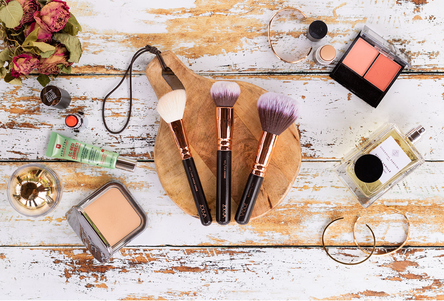 Les pinceaux pour le teint de Zoeva posés sur une planche ronde en bois au milieu de maquillage pour le teint