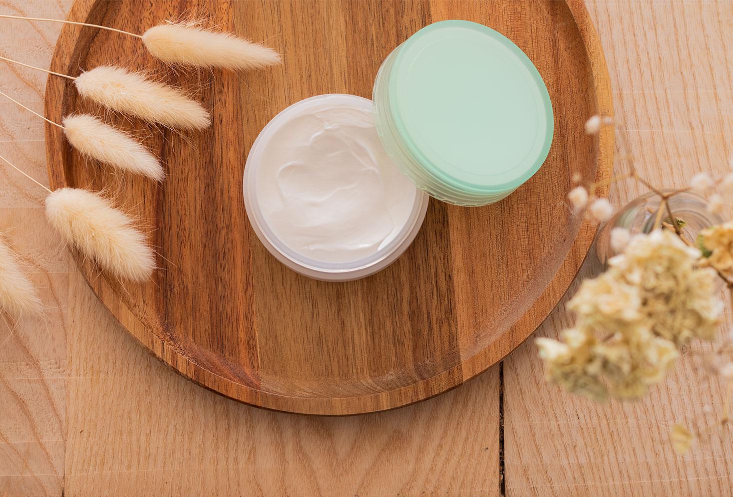 Flatlay de la crème anti-âge Esthética Pure Nature, posée sur un plateau en bois, ouverte pour un zoom sur la texture crémeuse et épaisse du produit