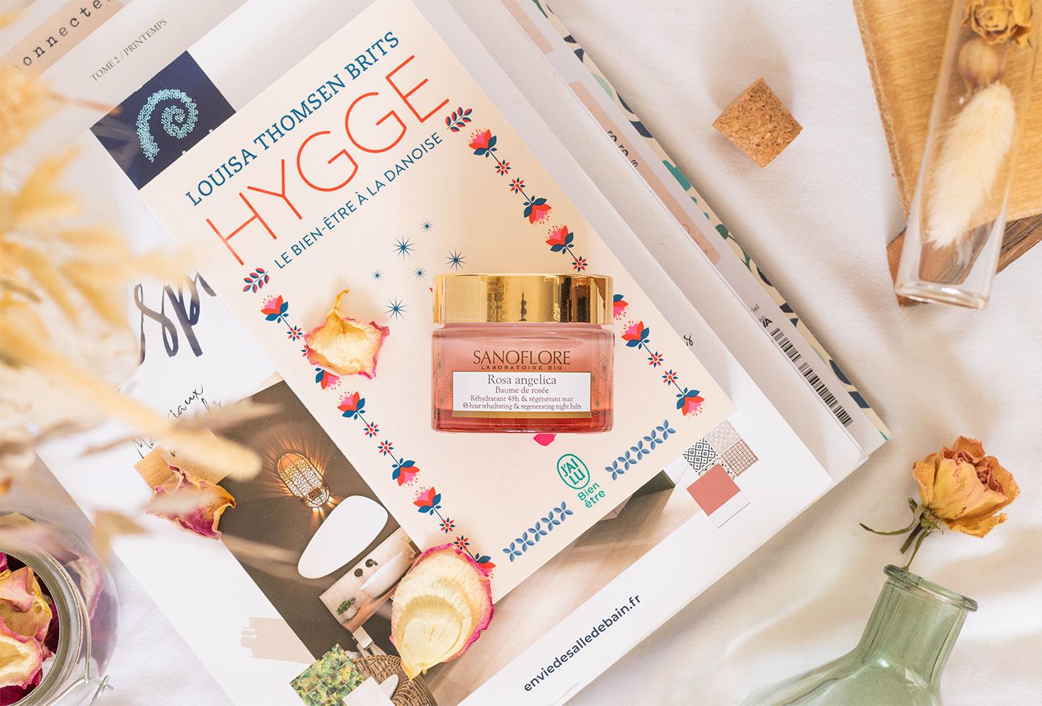 Le baume de rosée de la gamme Rosa Angelica de Sanoflore posé sur une pile de livres et de magazines