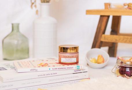 Le baume de rosée pour la nuit posé sur une pile de magazine et de livre dans une ambiance de salle de bain