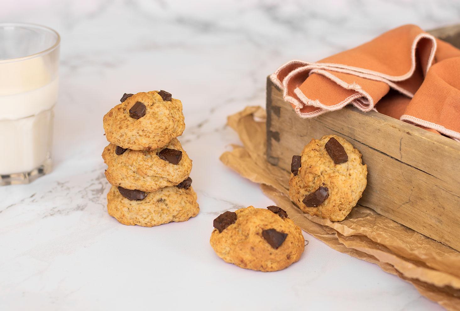 Cookies aux pépites de chocolat noir posés sur une table en marbre près d'une caisse en bois et d'un verre de lait