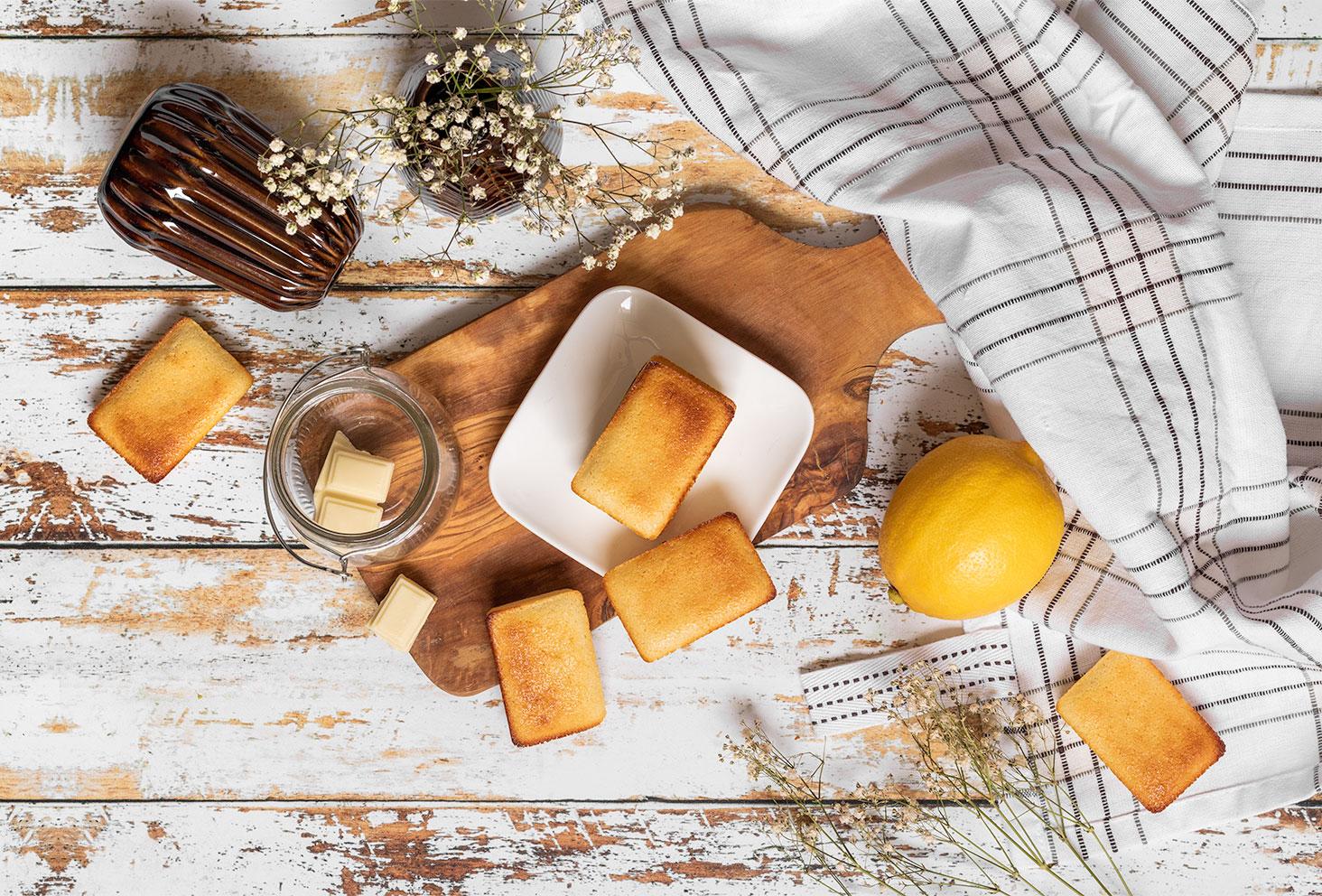 Stylisme culinaire en flatlay pour une recette de financiers au citron, sur une table en bois vintage à côté d'un torchon et de fleurs séchées