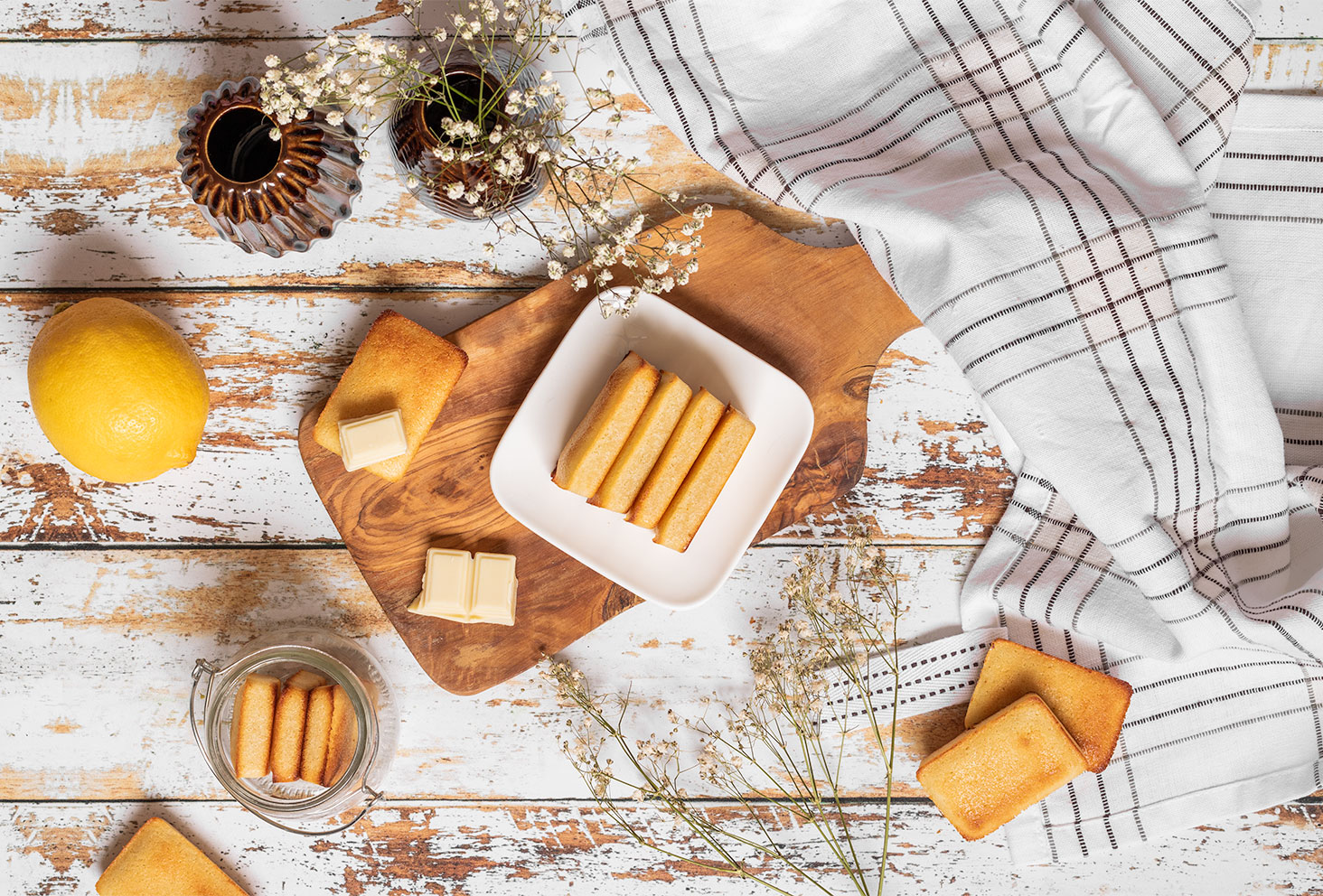 Des minis financiers au citron et au pépites de chocolat blanc, posés sur une planche à découper en bois, sur une table blanche en bois vintage avec un torchon et des fleurs séchées