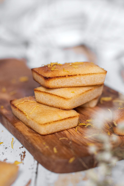 Des financiers au citron et au pépites de chocolat posés sur planche à découper en bois au milieu de zestes de citron