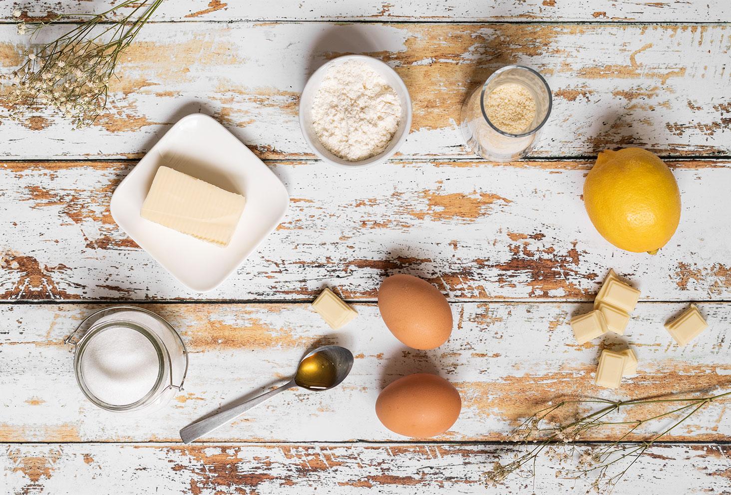 Les ingrédients nécessaires pour réaliser la recette facile de des financiers au citron et aux pépites de chocolat blanc, posés sur une table en bois vintage