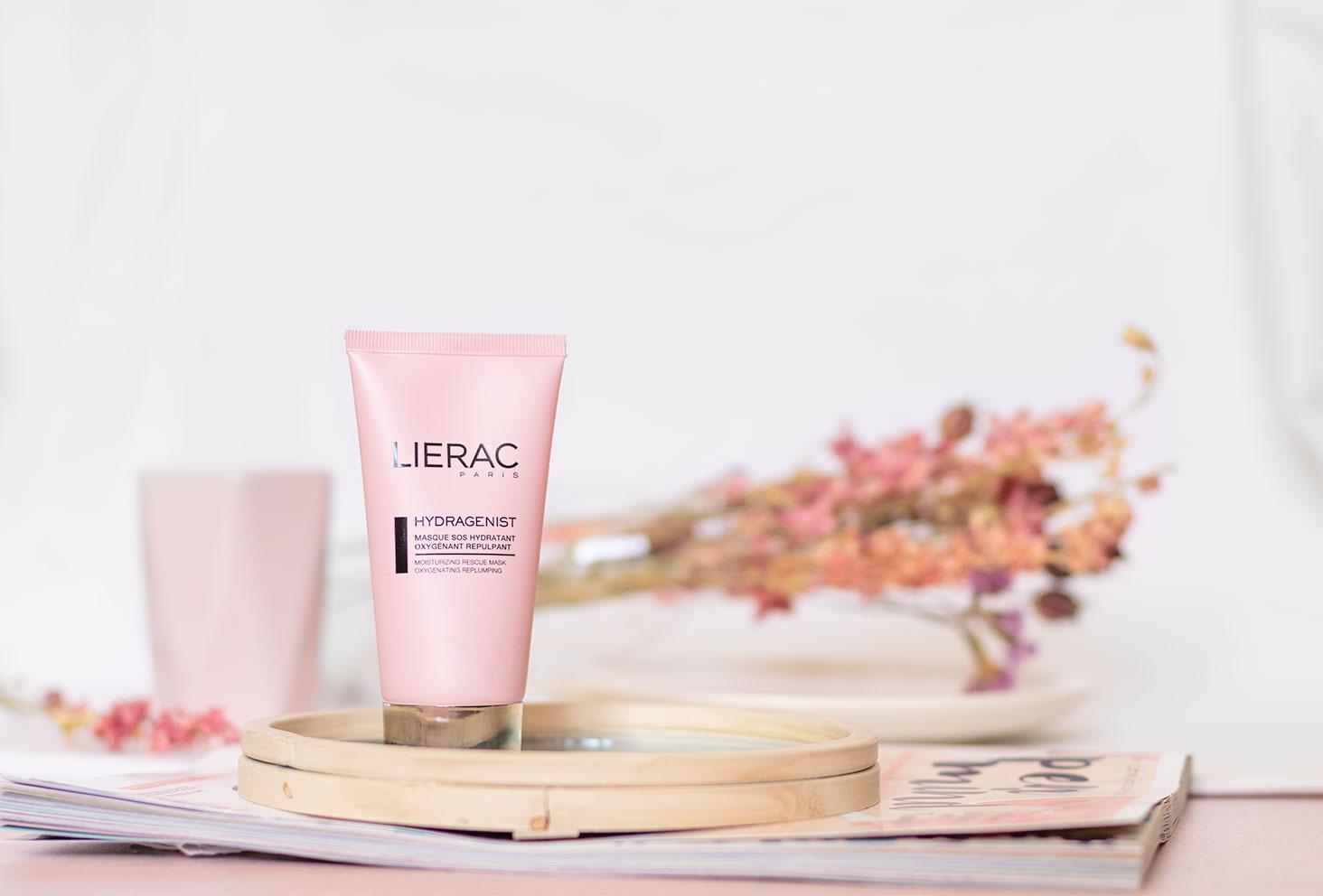 Le masque Hydragenist hydratant et oxygénant de Lierac posé sur un miroir devant un fond blanc et des fleurs séchées roses