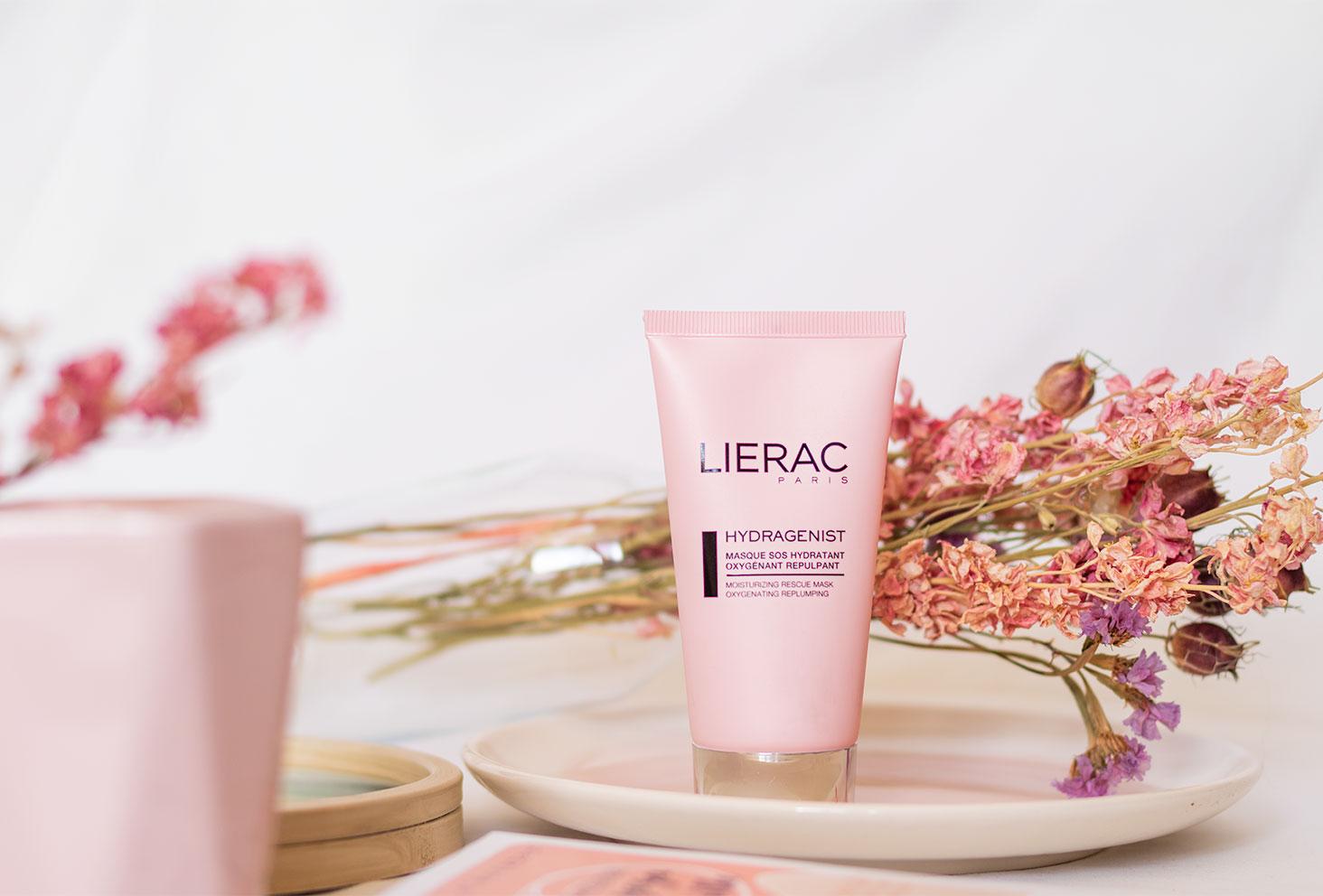 Le masque hydratant de Lierac posé dans une assiette rose en verre devant un bouquet de fleurs séchées roses