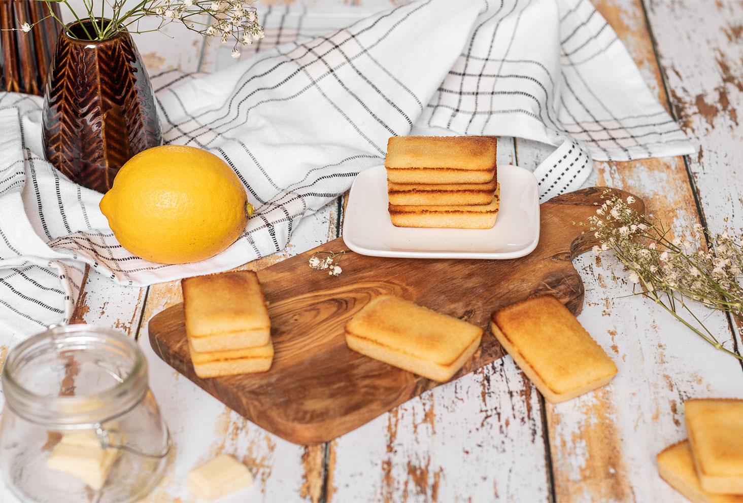Des petits financiers faciles à réaliser, au citron et chocolat blanc, posés sur une table en bois blanche vintage, dans un décor de cuisine authentique