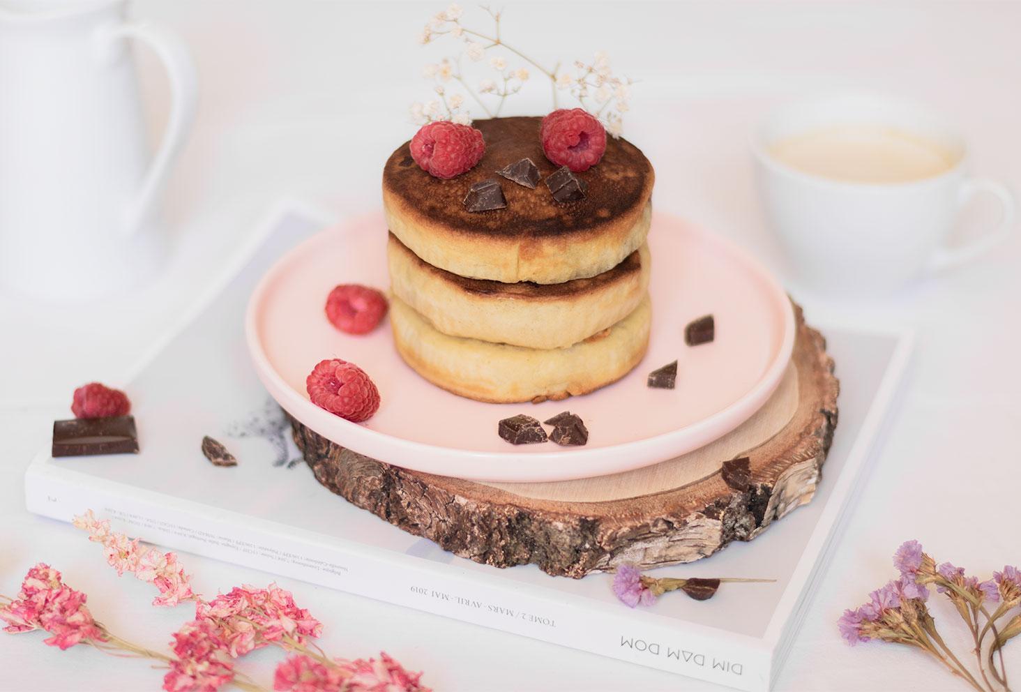 Des fluffy pancakes géant fourrés aux framboise et au chocolat noir posés dans une assiette rose avec un cappuccino