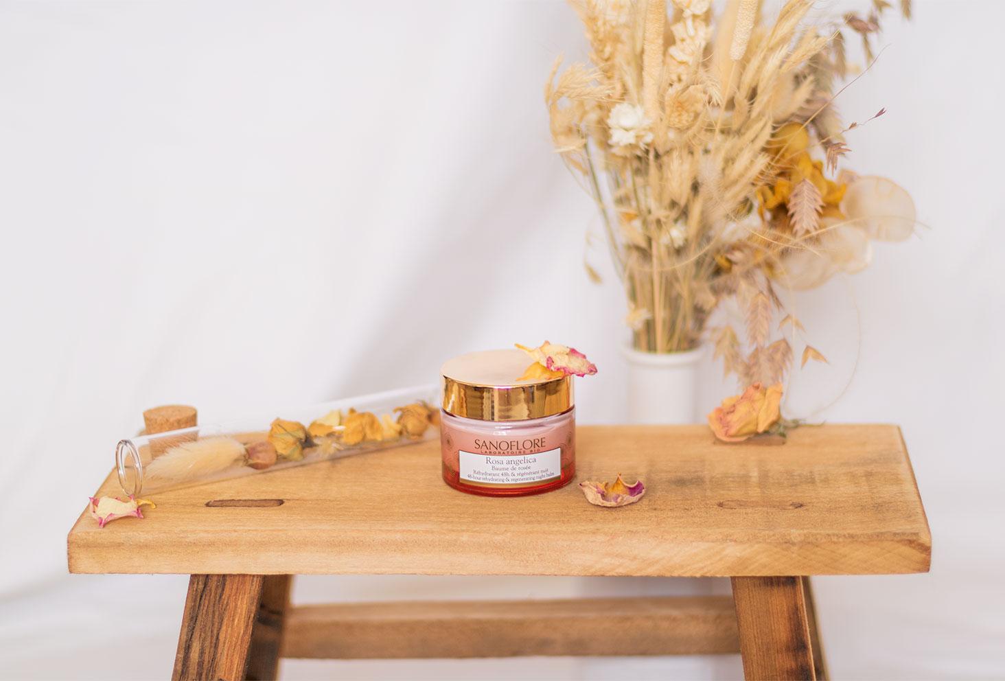 Le baume de rosée Rosa Angelica posé sur un tabouret en bois au milieu de fleurs séchées