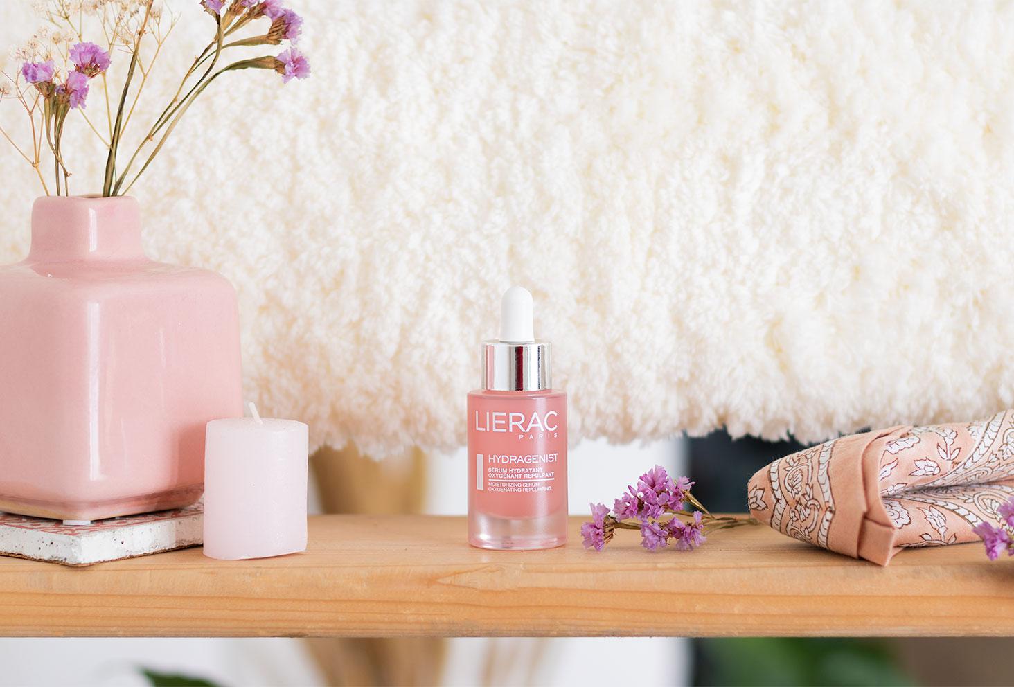 Le sérum hydratant et oxygénant de Lierac, dans un flacon rose en verre, sur une étagère en bois clair