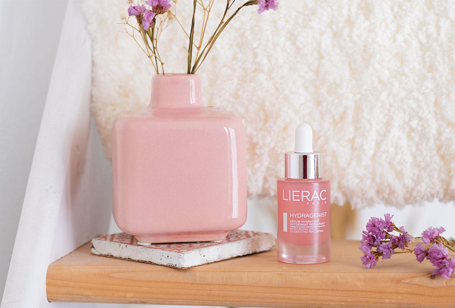 Le sérum Lierac hydratant dans son flacon en verre rose, sur une étagère en bois à côté d'un vase rose et de fleurs séchées violettes