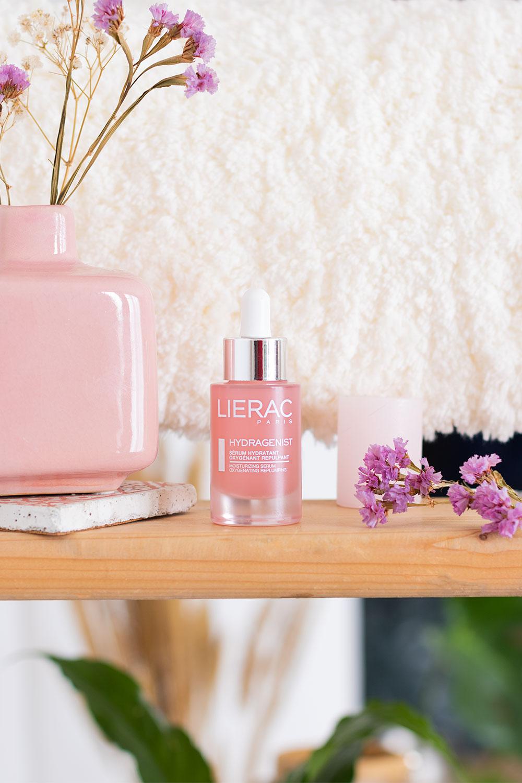 Sur une étagère en bois clair, le sérum Lierac posé à côté de fleurs séchées violettes