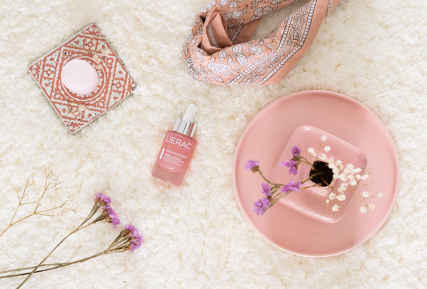 Le sérum oxygénant et hydratant de Lierac posé sur un tapis de bain en fausse fourrure blanche au milieu d'accessoires roses