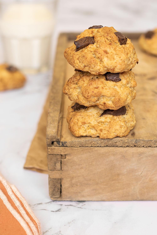 Zoom sur des cookies sans œufs aux pépites de chocolat noir, posés sur une caisse en bois près d'un verre de lait