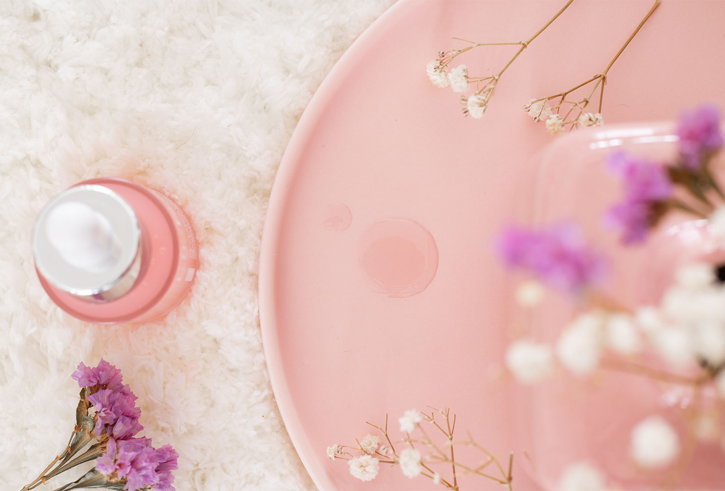 Zoom sur la texture gel et légère dans une assiette rose, au milieu de fleurs séchées, dans une assiette rose