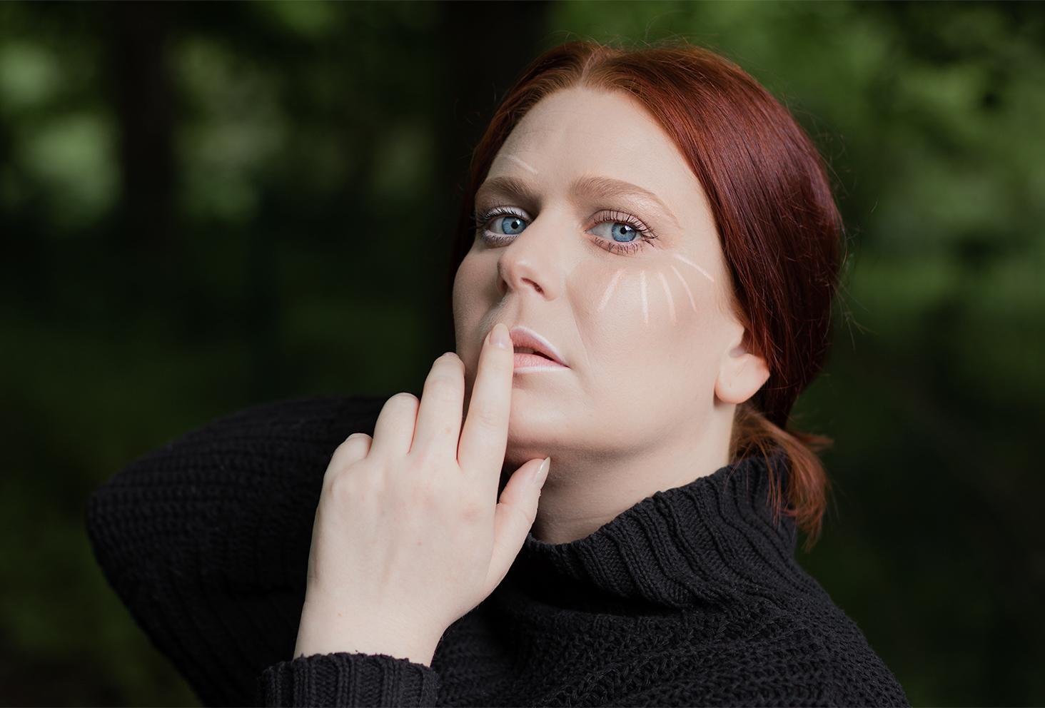 Un make-up géométrique pour parler des crises d'angoisse, les cheveux attachés, de profil, un doigt silencieux sur les lèvres