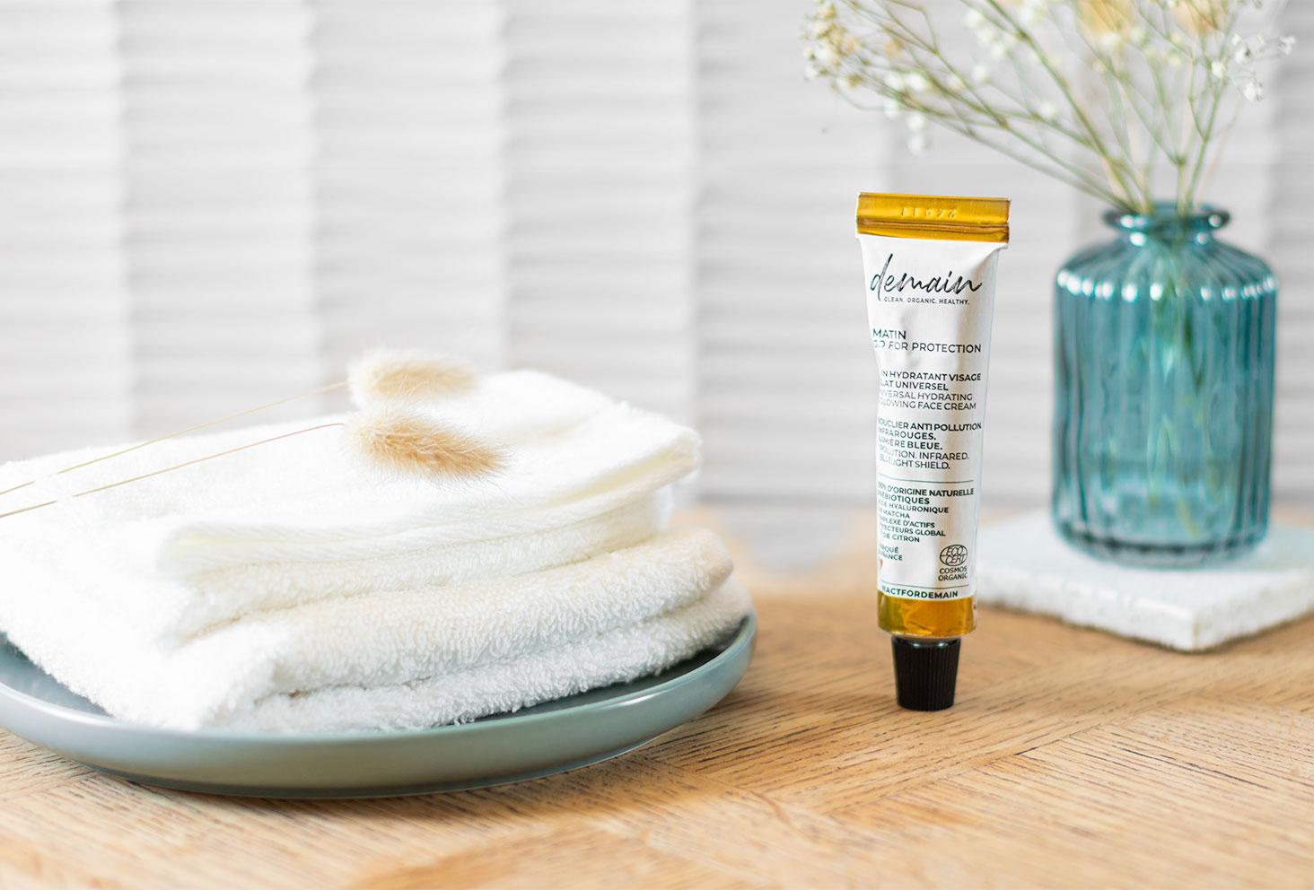 La crème hydratante Go For Protection de Demain Beauty, posé sur le meuble en bois de la salle de bain au milieu de serviettes