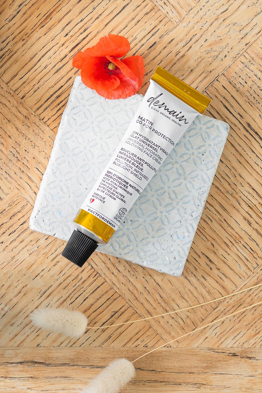 La crème hydratante visage de Demain Beauty posé sur un carreau de ciment avec un coquelicot