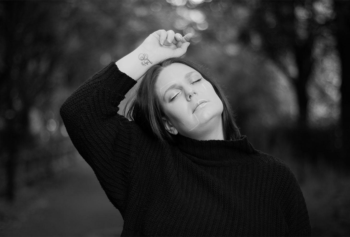 Portrait en noir et blanc au milieu d'arbres, un maquillage géométrique dessiné sur le visage, les yeux fermés la tête levée avec la main sur la tête