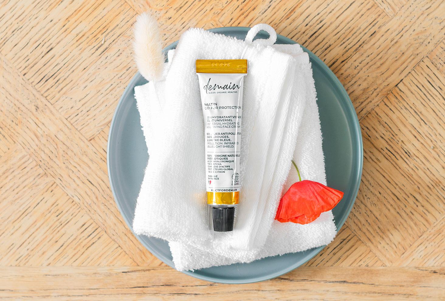 Le soin hydratant de Demain, posé sur une serviette blanche dans une assiette, sur un meuble en bois au milieu de fleurs