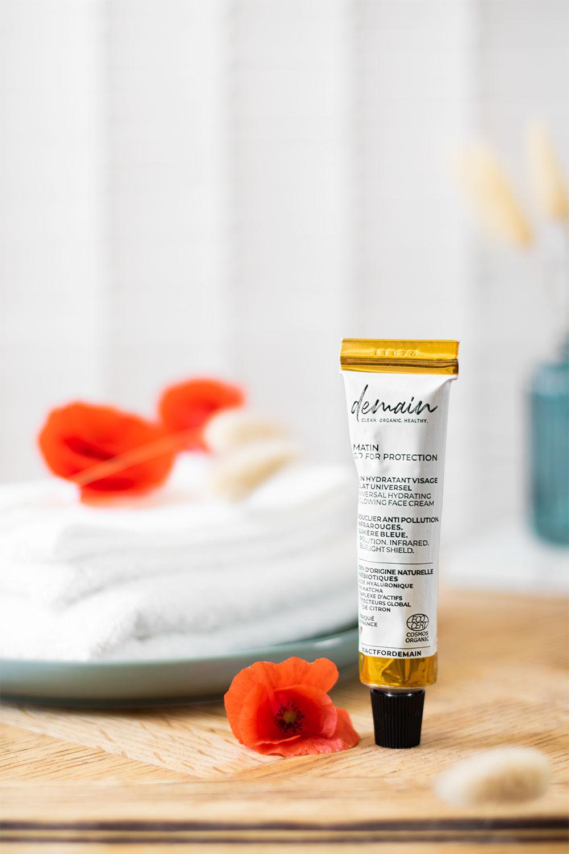 Le soin hydratant universel Go For Protection de Demain beauty, posé sur le meuble en bois de la salle de bain au milieu de coquelicot