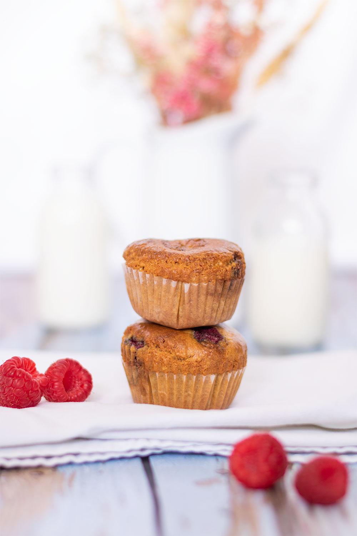 Zoom sur deux muffins aux framboises posé l'un sur l'autre au milieu de framboises sur un torchon blanc