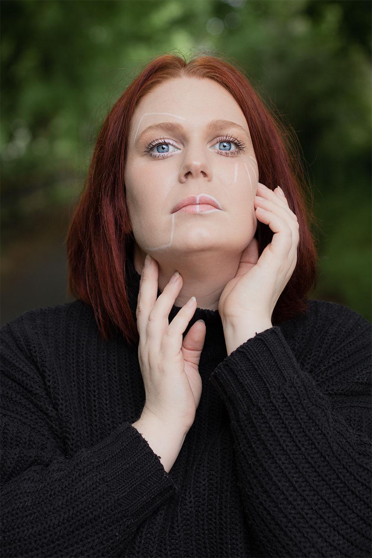 Photo portrait au milieu de grand arbres, un maquillage géométrique sur le visage, pour parler des crises d'angoisse