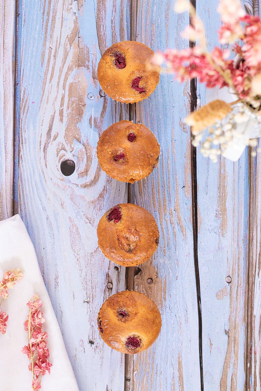 Une ligne de muffins aux framboises et à la noisette alignés sur une table en bois bleu vintage