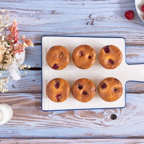 Des muffins aux framboises alignés sur une planche à découper en verre blanche, sur une table en bois bleutée