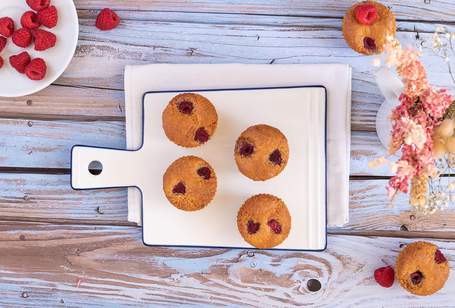 Muffins aux framboises et à la noisette, en flatlay posé sur une planche en verre blanche sur une table en bois bleutée