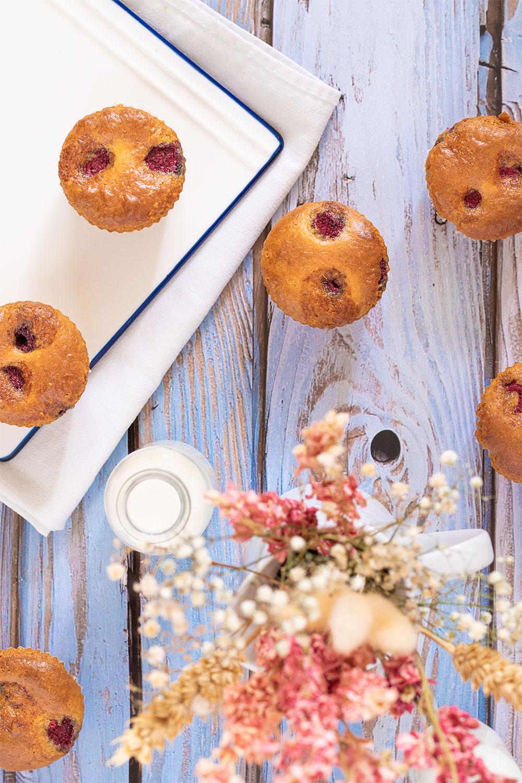 Zoom sur des muffins aux framboises éparpillés sur une table en bois vintage, avec un bouquet de fleurs séchées