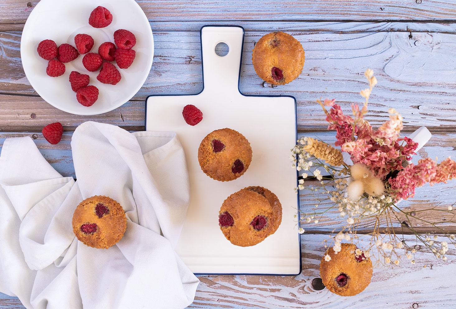 Muffins aux framboises posés sur une planche blanche au milieu de framboises et de fleurs séchées