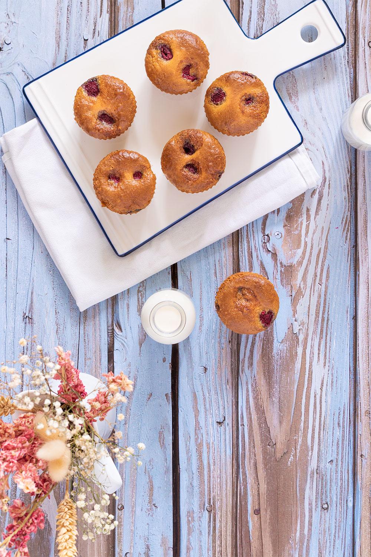 Des muffins aux framboises posés sur une planche blanche, à côté de bouteille de lait et d'un bouquet de fleurs séchés