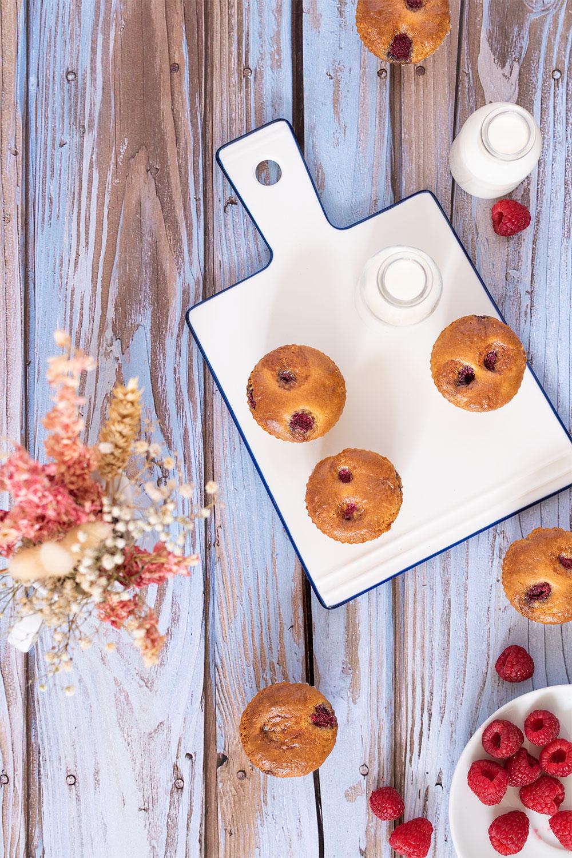 Muffins à la noisette et aux framboises posés sur une table en bois bleu vintage, avec une planche à découper en verre blanche