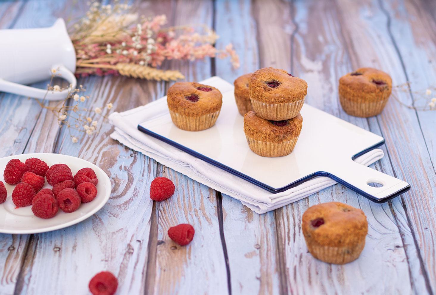Recette de muffins aux framboises et à la noisette, sur une planche en verre, au milieu de fleurs séchées et de framboises fraîches