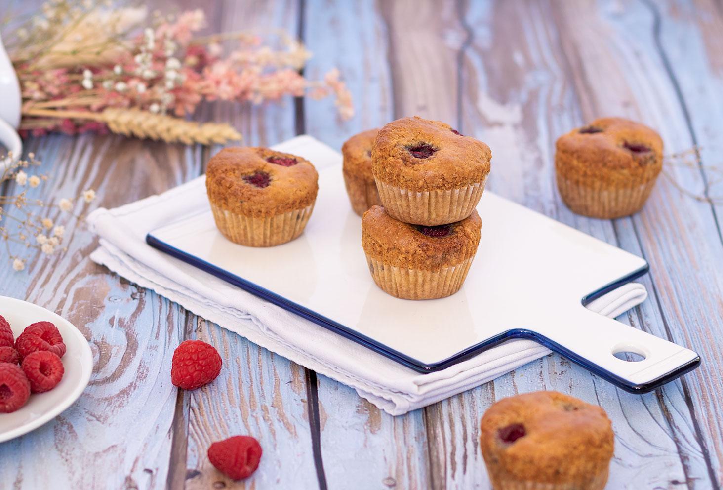 Zoom sur des muffins aux framboises sur une planche blanche en verre au milieu de framboises fraîches et de fleurs séchées