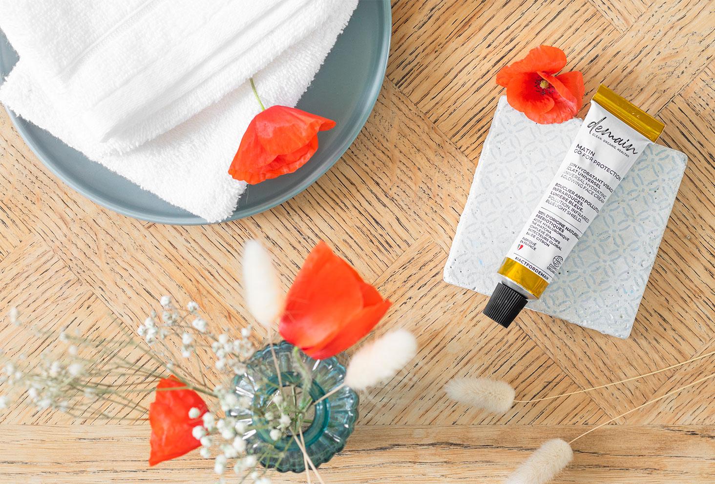 La crème hydratante Go For Protection de la marque Demain, posée sur un carreau de ciment bleu, au milieu de fleurs et de coquelicots