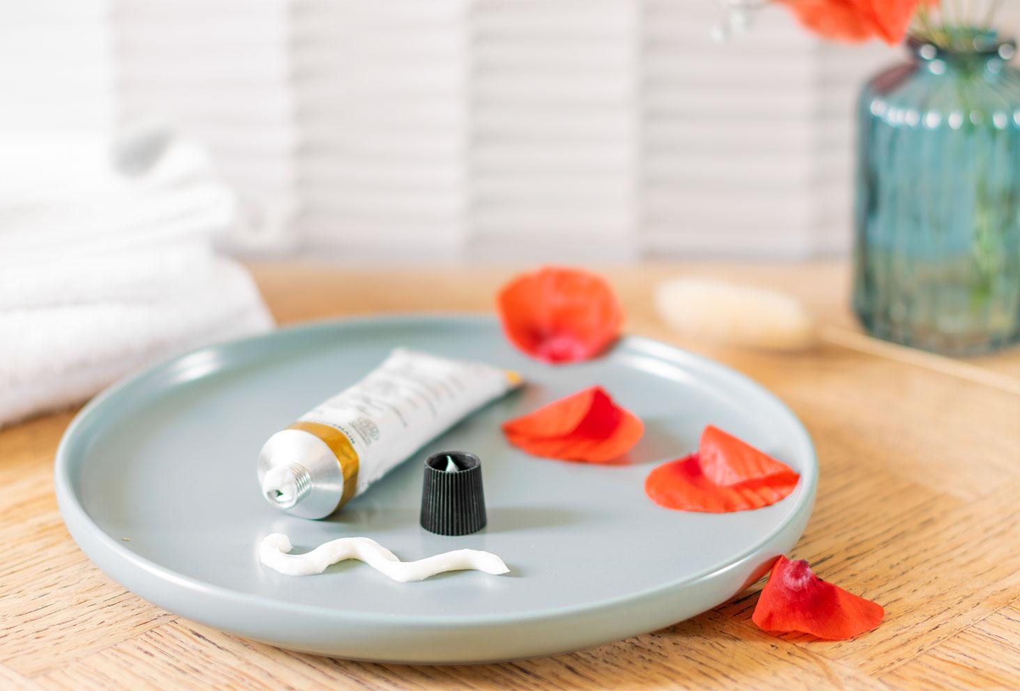 La texture du soin visage Go For Protection dans une assiette verte au milieu de pétales de coquelicots