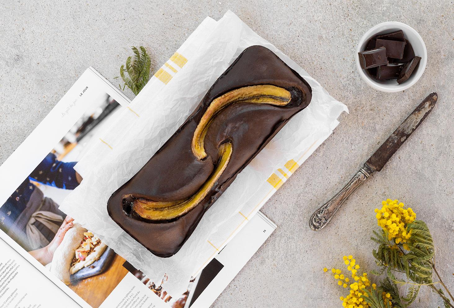 Un banana bread protéiné au chocolat avec la poudre Fit Chocolate, posé sur un torchon jaune et blanc, à côté de fleurs jaunes et d'un magazine ouvert