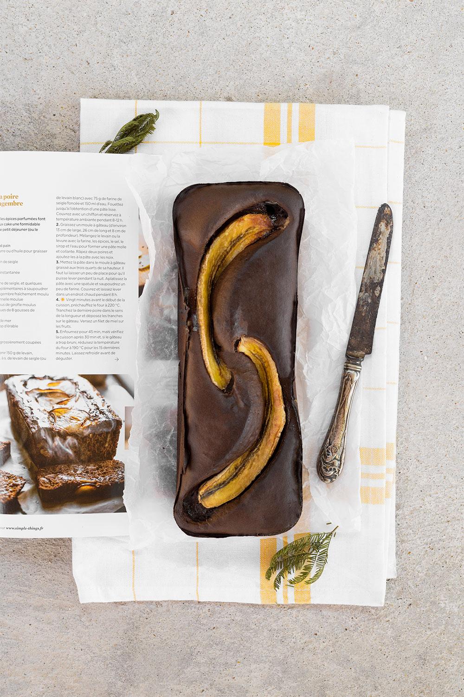 Banana bread au chocolat protéiné avec le Fit Chocolate de Natural Mojo, posé sur un magazine et un torchon, vu de haut