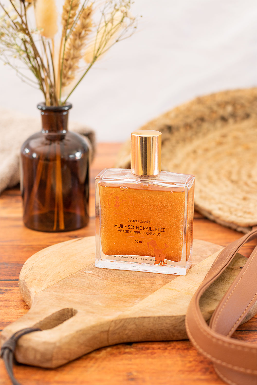 L'huile sèche pailletée de secrets de miel posée sur une planche à découper en bois devant un bouquet de fleurs séchées et un sac de plage en paille