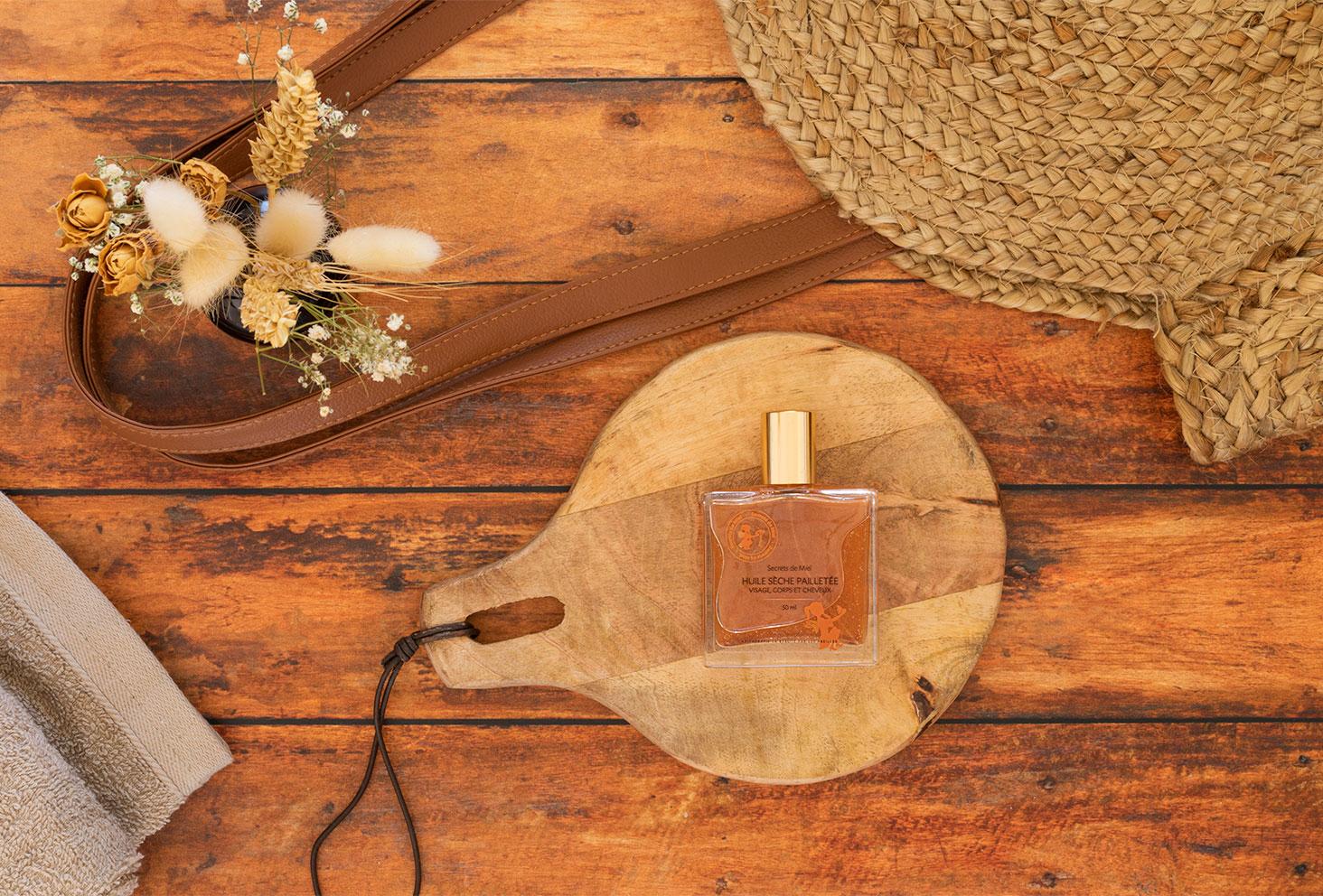 L'huile sèche pailletée de Secrets de Miel sur une planche en bois à côté d'un sac de plage en paille