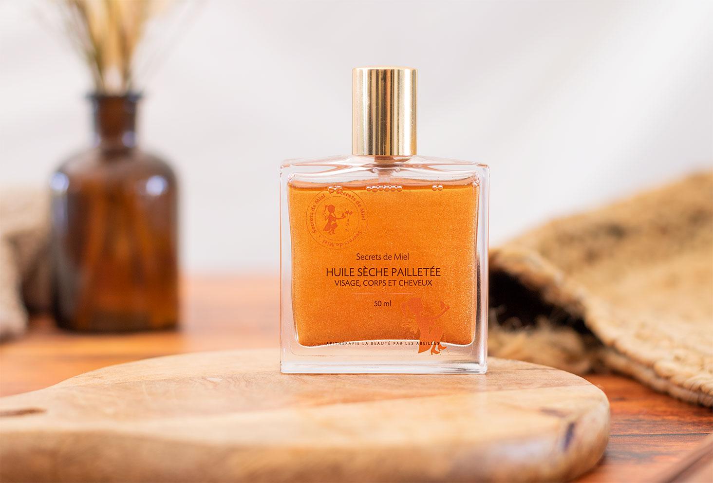 Zoom sur le packaging en verre de l'huile sèche pailletée visage, corps et cheveux, de la marque Secrets de Miel posée sur un planche à découper en bois ronde