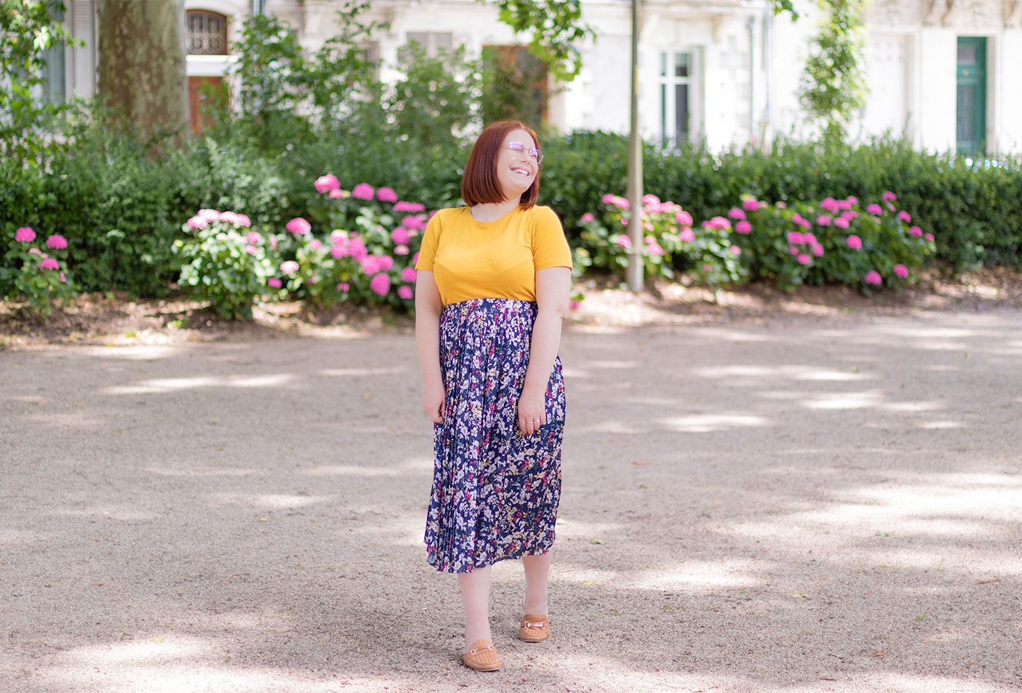 En jupe midi à fleurs et t-shirt jaune, au milieu d'un jardin fleuri, tendances pour l'été