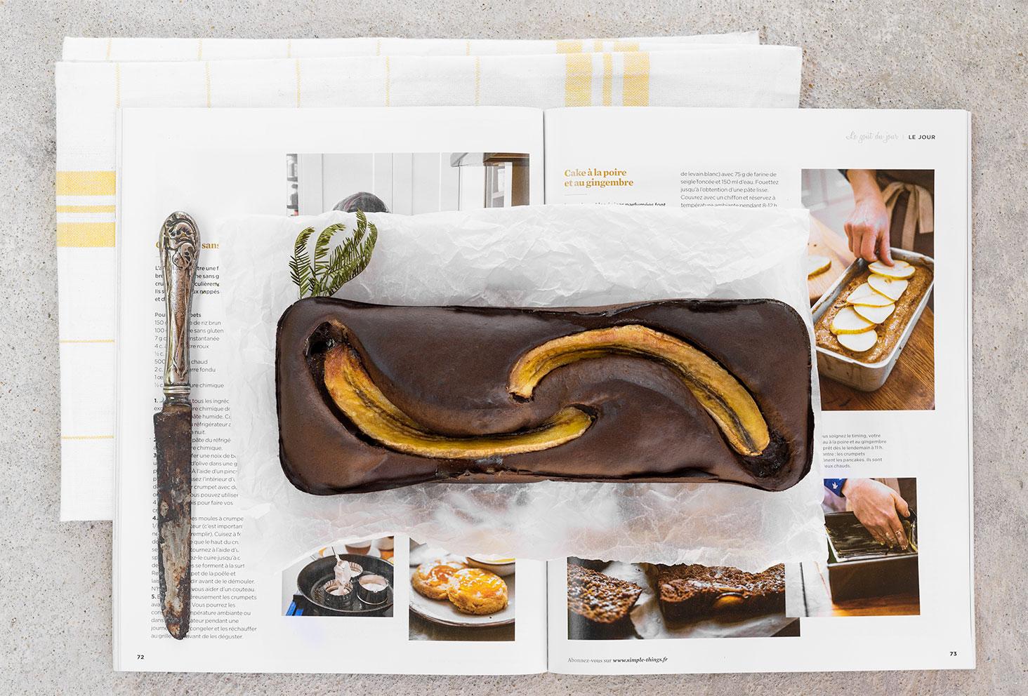 Un banana bread au chocolat protéiné posé sur du papier sulfurisé, sur un magazine culinaire